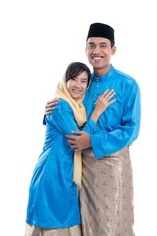 Азиатская мусульманская пара, держащая руку, изолированную над белой