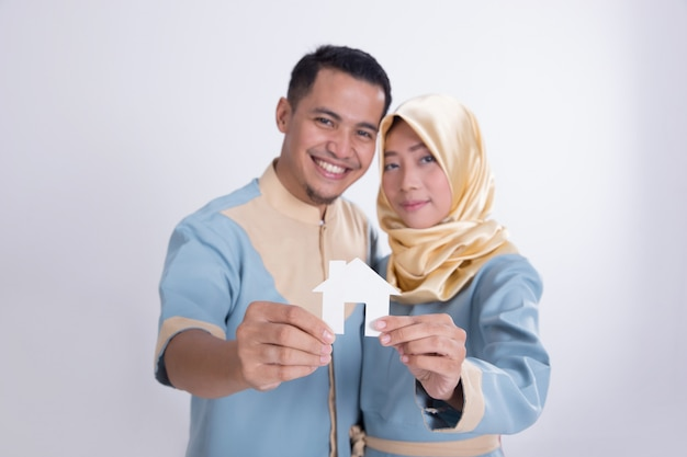 Muslim asian couple holding home sign