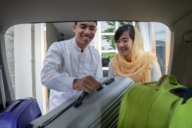 Muslim asian couple put suitcase in the car trunk