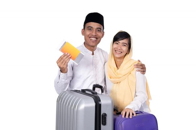Мусульманская азиатская пара с чемоданом путешествия