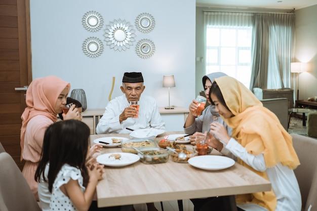 Мусульманская азиатская семья и бабушка и дедушка прерывают пост на рамадан. ифтар обеденный перерыв