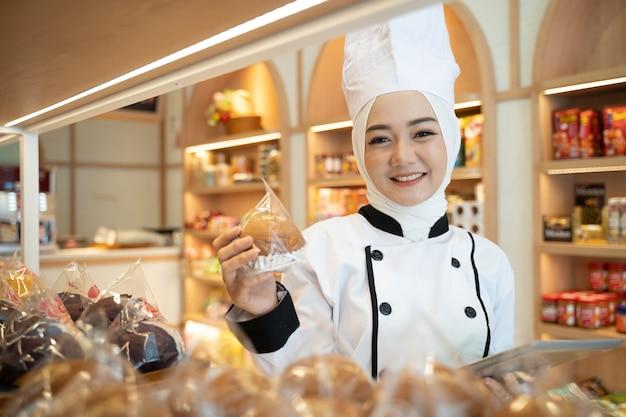 ディスプレイトレイに彼女の製品を保持し、タブレットメニューを見ているイスラム教徒のアジアの女性パン屋