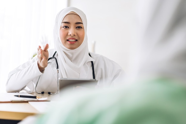 Muslim asian female doctor consulting and check up information with muslim woman