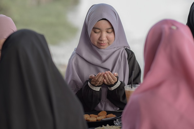 Азиатские друзья-мусульмане молятся вместе в кафе