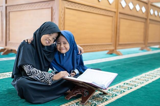 Мусульманский азиатский ребенок читает коран