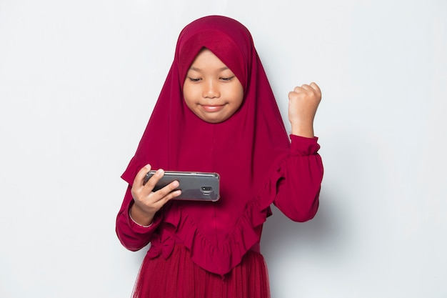 Muslim asian little girl using smart phone game on white background