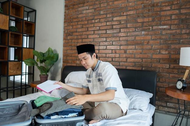 荷物の紙のチェックリストを保持しているイスラム教徒のアジア人男性