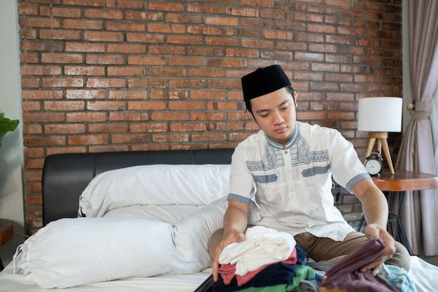 Muslim asian male preparing and packing clothes