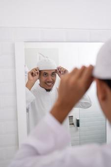 イスラム教徒のアジア人男性が鏡を見て、イスラムの帽子や帽子をかぶってモスクに行く前に服を着る