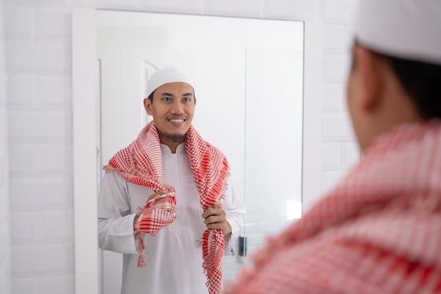 鏡を見て、モスクに行く前に服を着るイスラム教徒のアジア人男性