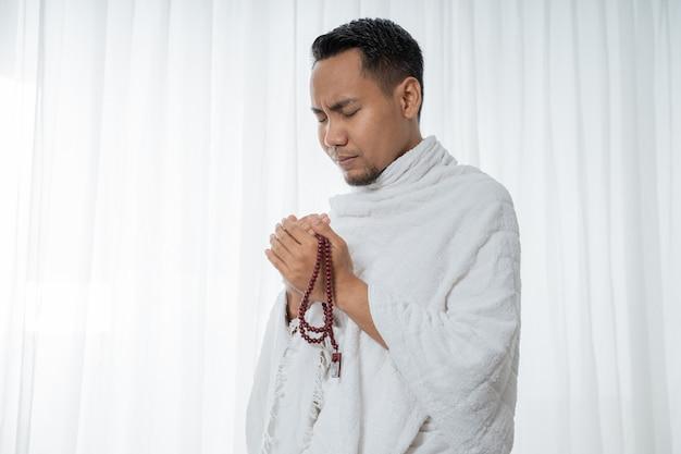 数珠で祈るイスラム教徒のアジア人