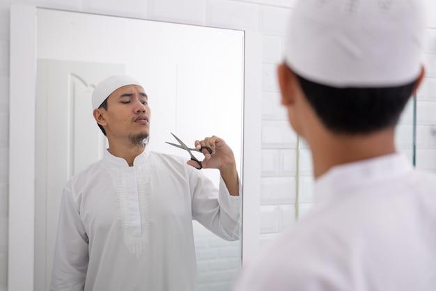 はさみを使用して彼のひげを剃るのがわからないイスラム教徒のアジア人