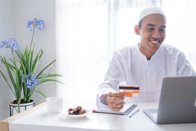 オンラインショップの支払い取引にクレジットカードを使用しているイスラム教徒のアジア人男性