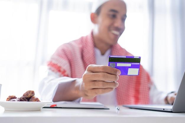 온라인 상점 결제 거래에 신용 카드를 사용하는 이슬람 아시아 남자