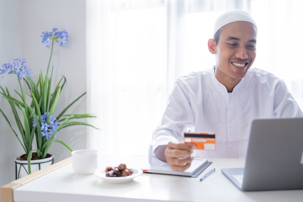 Muslim asian man using credit card for online shop payment transaction