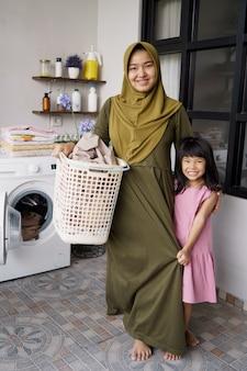 洗濯機の近くの洗濯室でイスラム教徒のアジアの母と子の女の子の小さなヘルパー
