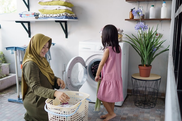Muslim asian mother and child girl little helper in laundry room near washing machine