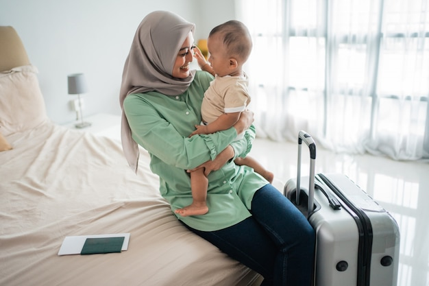 Muslim asian mothers carry their babies while sitting on the bed
