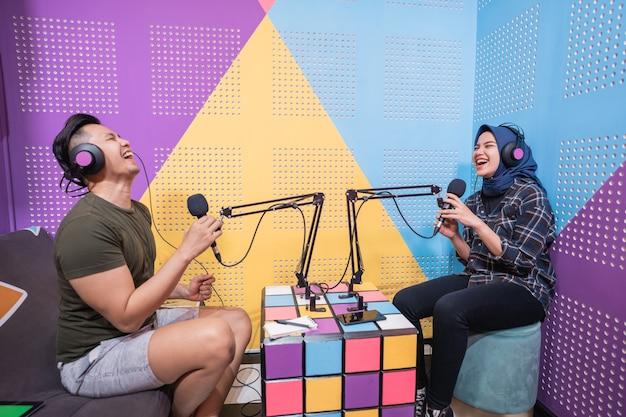 一緒にポッドキャストスタジオで話しているイスラム教徒のアジアの女性と男性