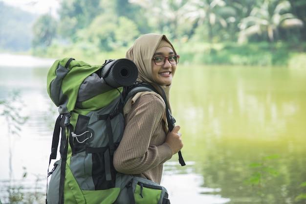 Мусульманская азиатская женщина турист с рюкзаком