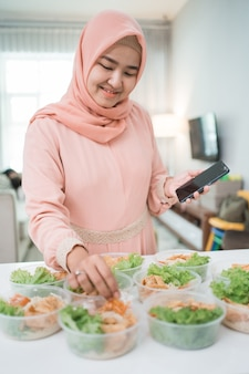 Muslim asian woman home catering service preparing lunch box for takeaway food online order