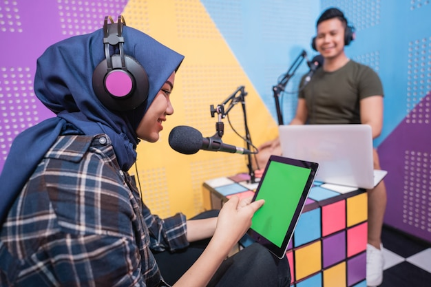 Muslim asian woman and man talking on podcast studio together