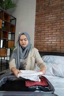 スーツケースを準備するイスラム教徒のアジアの女性