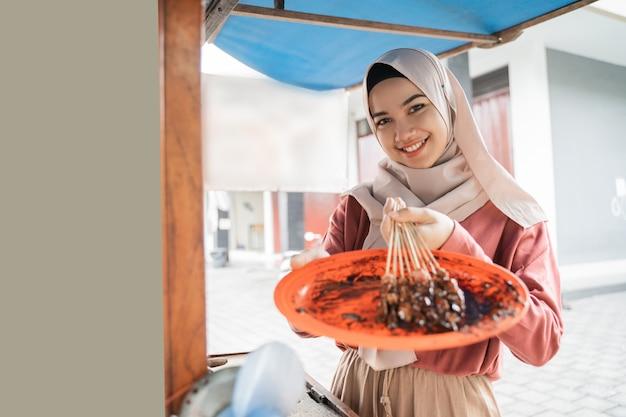 彼女のフードカートでチキンサテを販売するイスラム教徒のアジアの女性
