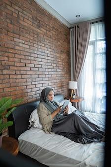 침대에 앉아 태블릿을 사용하여 이슬람 아시아 여자