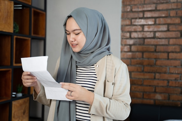Muslim asian woman with hijab looking at paper