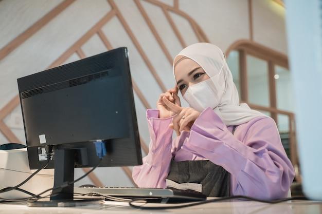 オフィスで保護のための医療用フェイスマスクを着用しながらpcを使用して作業しているイスラム教徒のアジアの女性