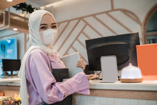Muslim asian woman working using pc while wearing medical face mask for protection in the office