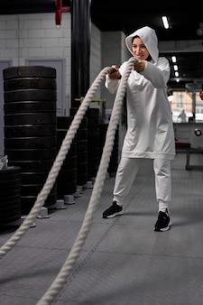 ヒジャーブのイスラム教徒のアスリートの女性は、決定的で集中的な機能トレーニングアスレチックフィットネススポーツ活動の自信を強化するように見える重いロープで働いています