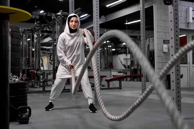 クロスフィットジムコピースペースでロープを使って運動するイスラム教徒の運動女性自信動機スポーツライフスタイル活動趣味健康強力な女性らしさトレーニングコンセプト