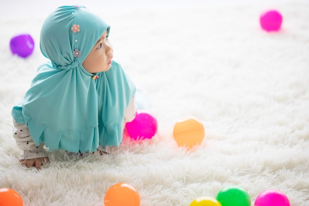 Muslim baby plays with colorful toys in the living room.