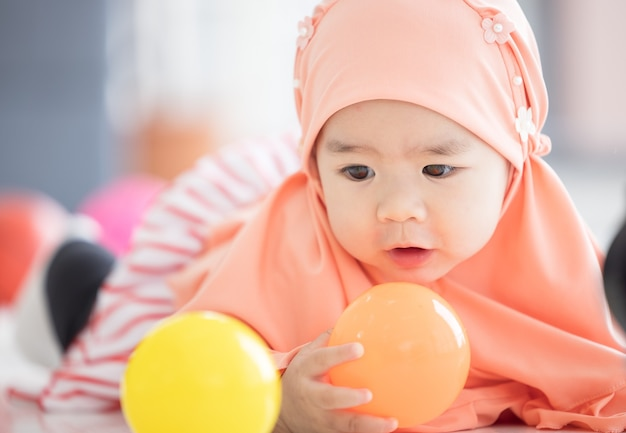 Muslim baby plays with colorful toys in the living room
