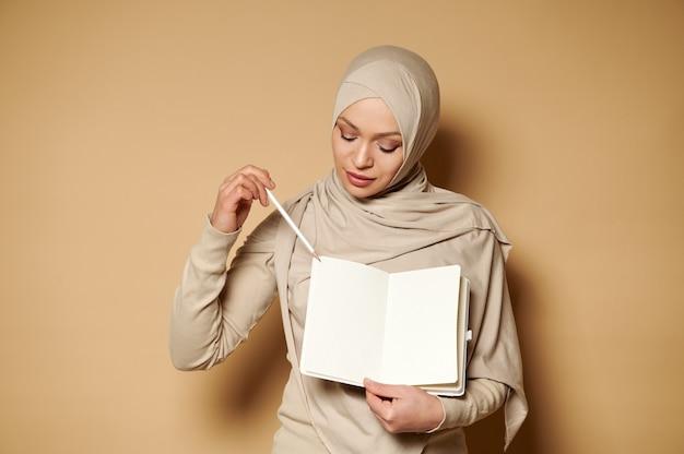 ベージュのヒジャーブでイスラム教徒の美しいアラビアの女性
