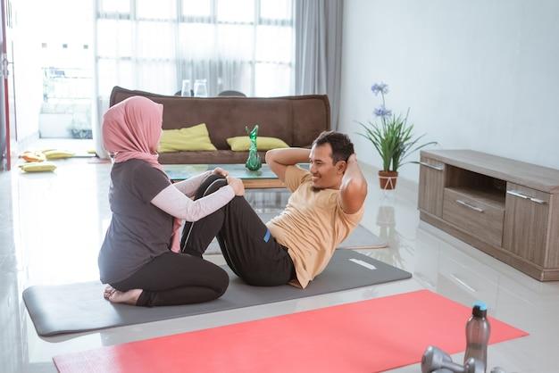 イスラム教徒の美しい女性と夫が一緒に座っています。自宅で運動するカップル