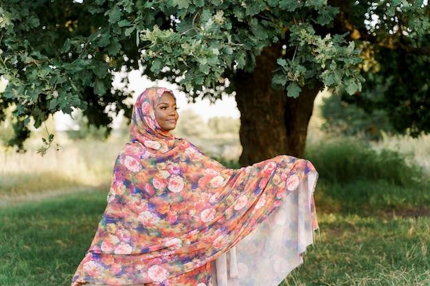 이슬람 흑인 여성 아프리카 민족은 전통적인 다채로운 hijab 미소를 착용하고 녹색 나무 아래에서 오른쪽으로 보입니다.