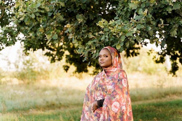 이슬람 흑인 여성 아프리카 민족은 전통적인 다채로운 히잡 미소를 입고 녹색 나무 아래에 머물러 있습니다.