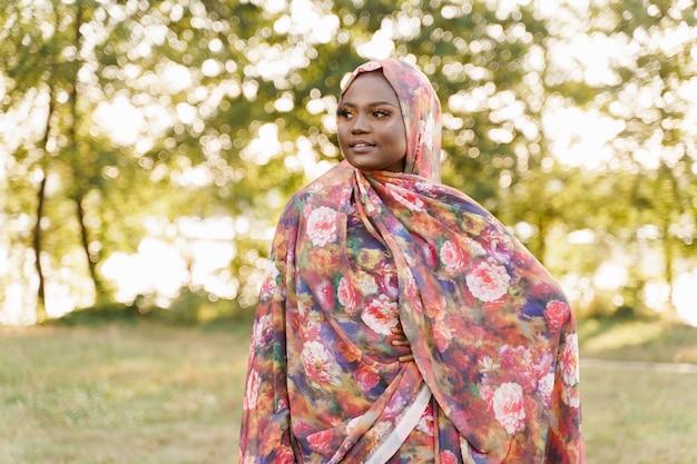 이슬람 흑인 여성 아프리카 민족은 녹색 초원에 전통적인 다채로운 히잡 미소를 weared