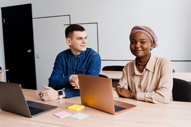 이슬람 흑인 여자와 노트북과 백인 남자. 다민족 부부는 비즈니스 프로젝트에서 온라인으로 함께 작동합니다.