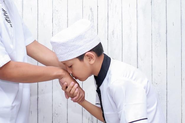 Muslim boy greeting and asking forgiveness by kissing hand at ramadan and eid mubarak
