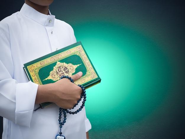 Мусульманский мальчик, держащий святую книгу аллаха или мусульманского бога