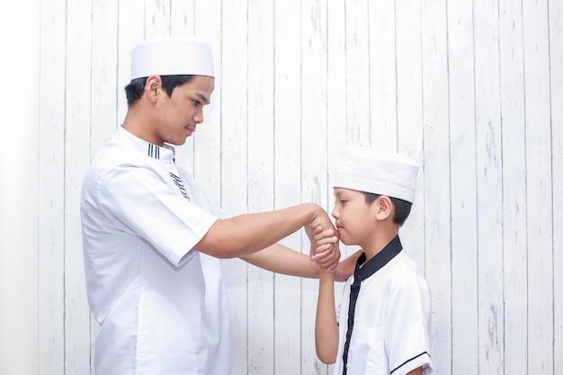Мальчик-мусульманин целует руку отца для прощения на ид мубарак в традиционной одежде