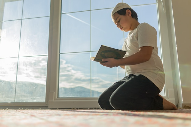 Muslim boy reading quran and praying for god