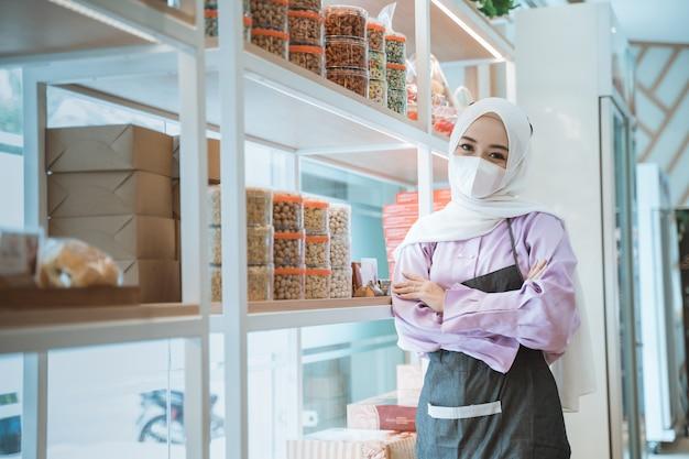 新しい通常の開店中に彼女の店の窓の隣に立っている衣装を着た人を待っているマスクを持つイスラム教徒のビジネスオーナー