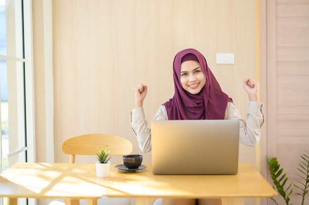 A muslim business woman wearing hijab working with her laptop in coffee shop