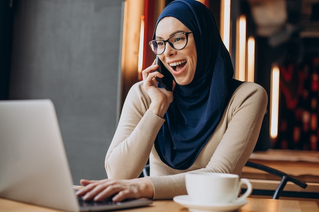 Muslim business woman working on computer in a cafe