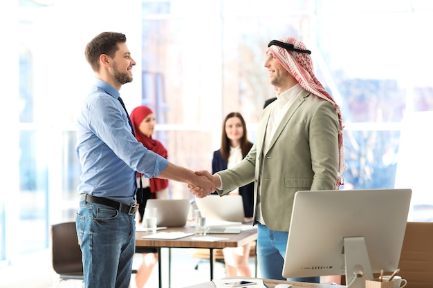 사무실에서 동료와 악수하는 이슬람 사업가